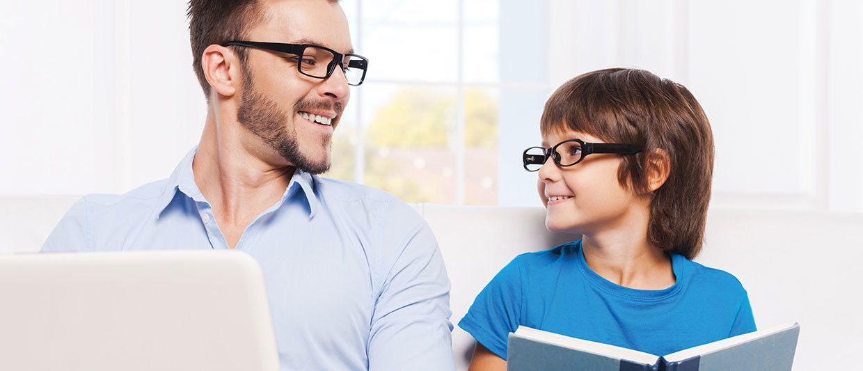 father and son reading books and wearing glasses