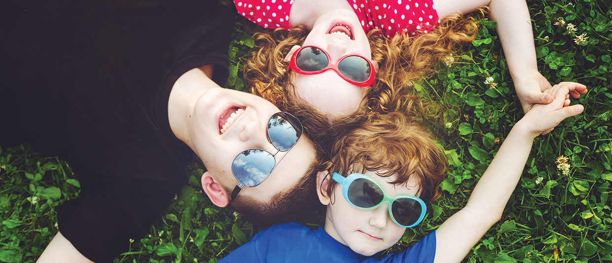 group of people lying on the grass wearing sunglasses